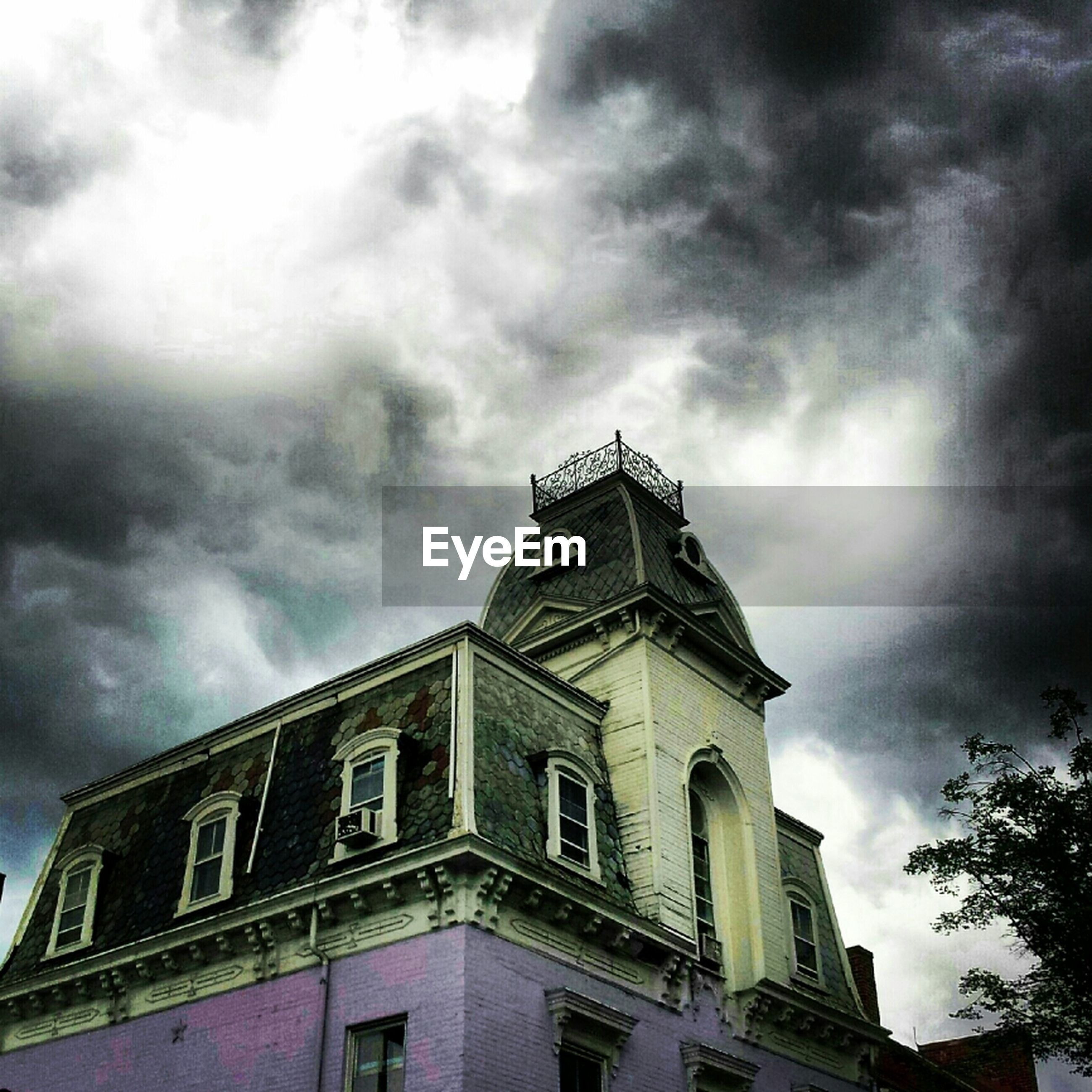 architecture, building exterior, built structure, low angle view, sky, cloud - sky, cloudy, cloud, overcast, weather, building, high section, outdoors, window, day, no people, storm cloud, city, religion, church