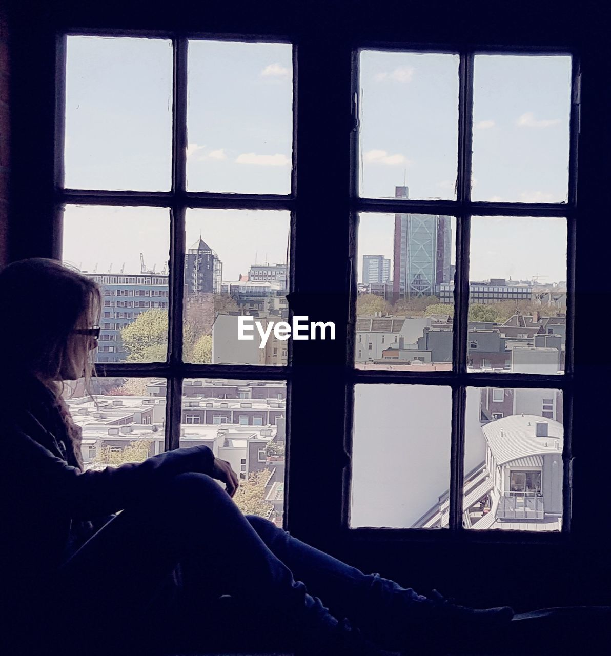 Side View Of Woman Sitting By Window In City