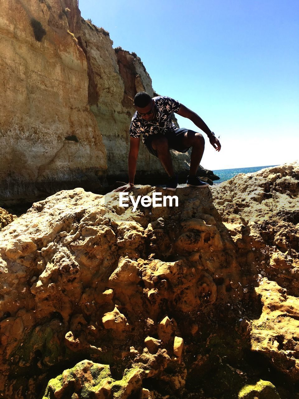 rock, solid, rock - object, sky, rock formation, nature, real people, day, clear sky, sunlight, one person, full length, leisure activity, lifestyles, outdoors, men, mountain, low angle view, adventure