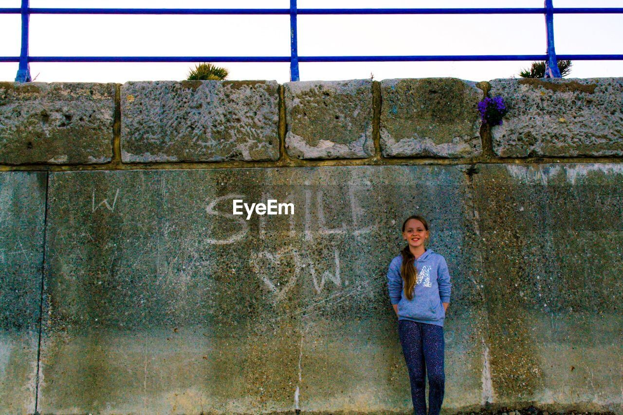 Portrait of girl standing by wall