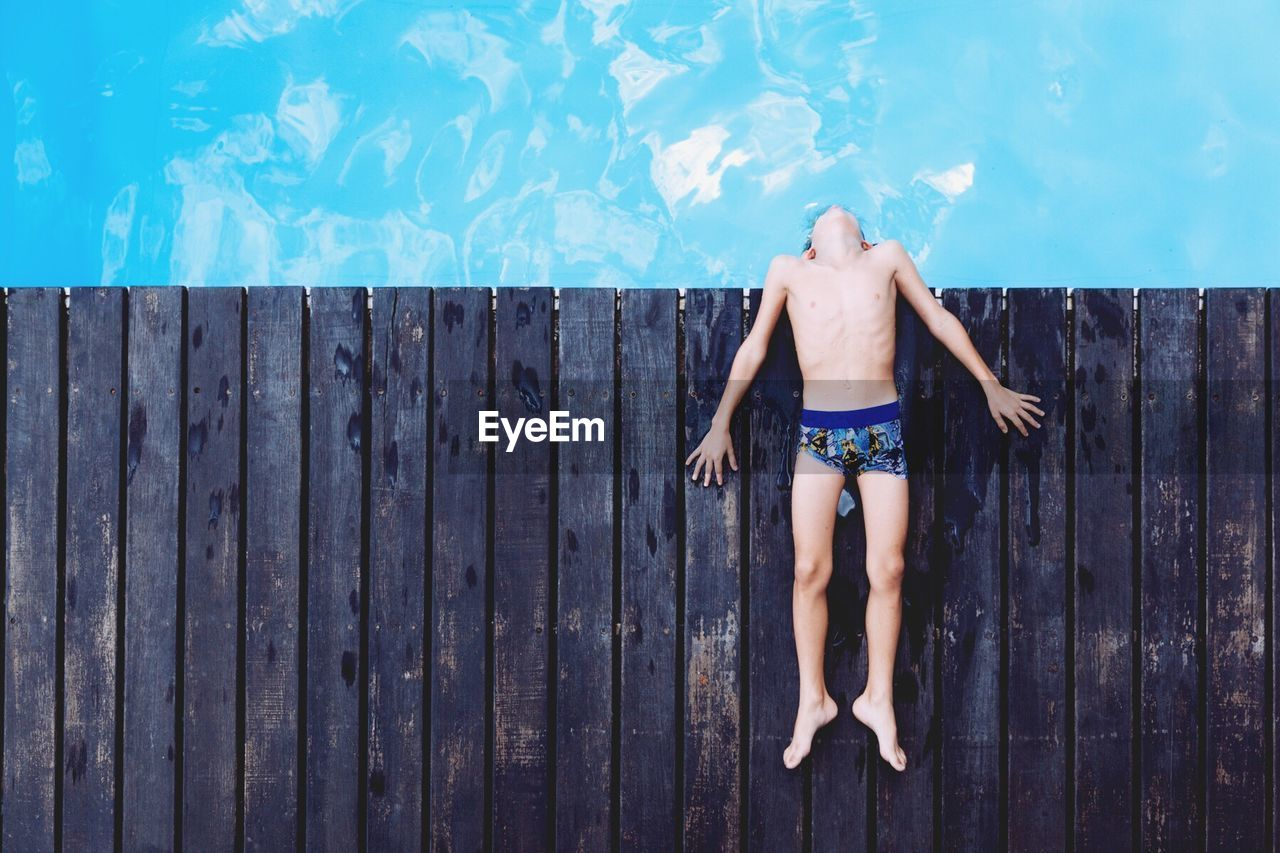 High Angle View Of Boy Lying On Wooden Deck By Swimming Pool