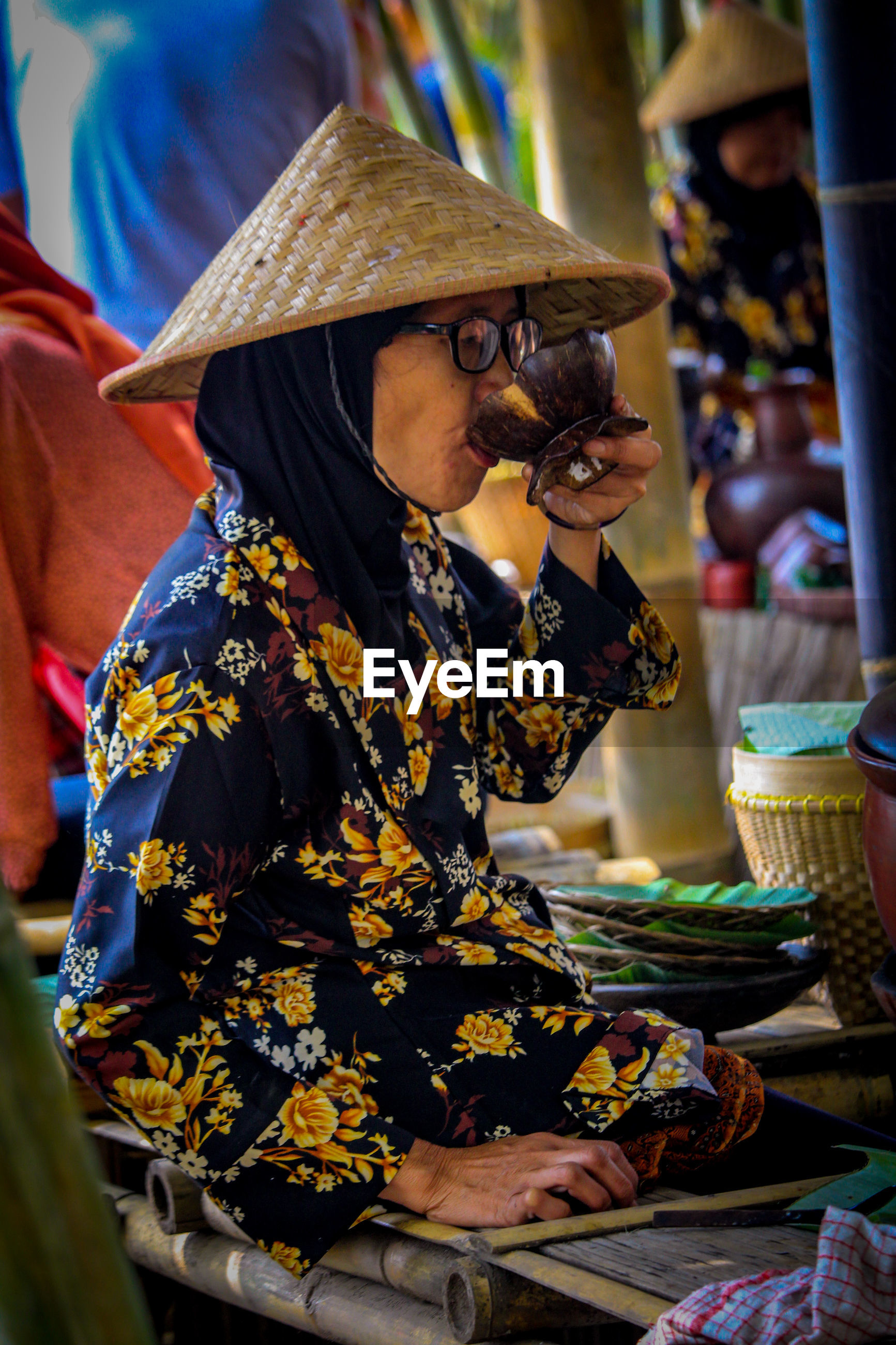 Woman drinking from bowl in shop