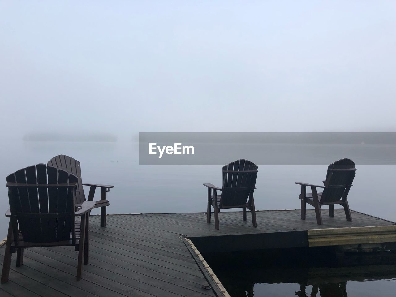 Empty chairs on pier over lake against sky
