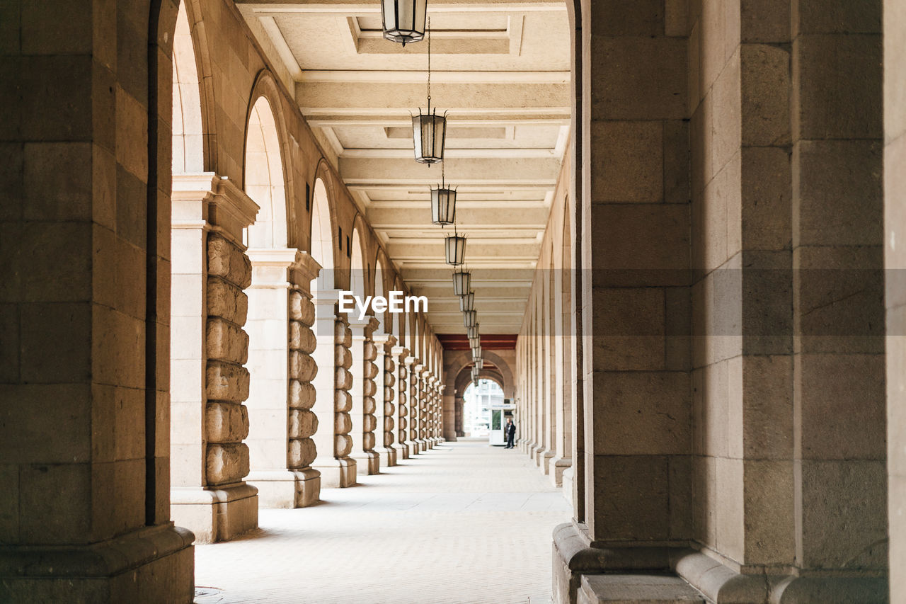 architecture, built structure, arcade, direction, building, the way forward, corridor, in a row, architectural column, arch, rear view, one person, the past, full length, colonnade, day, indoors, real people, history, diminishing perspective, ceiling