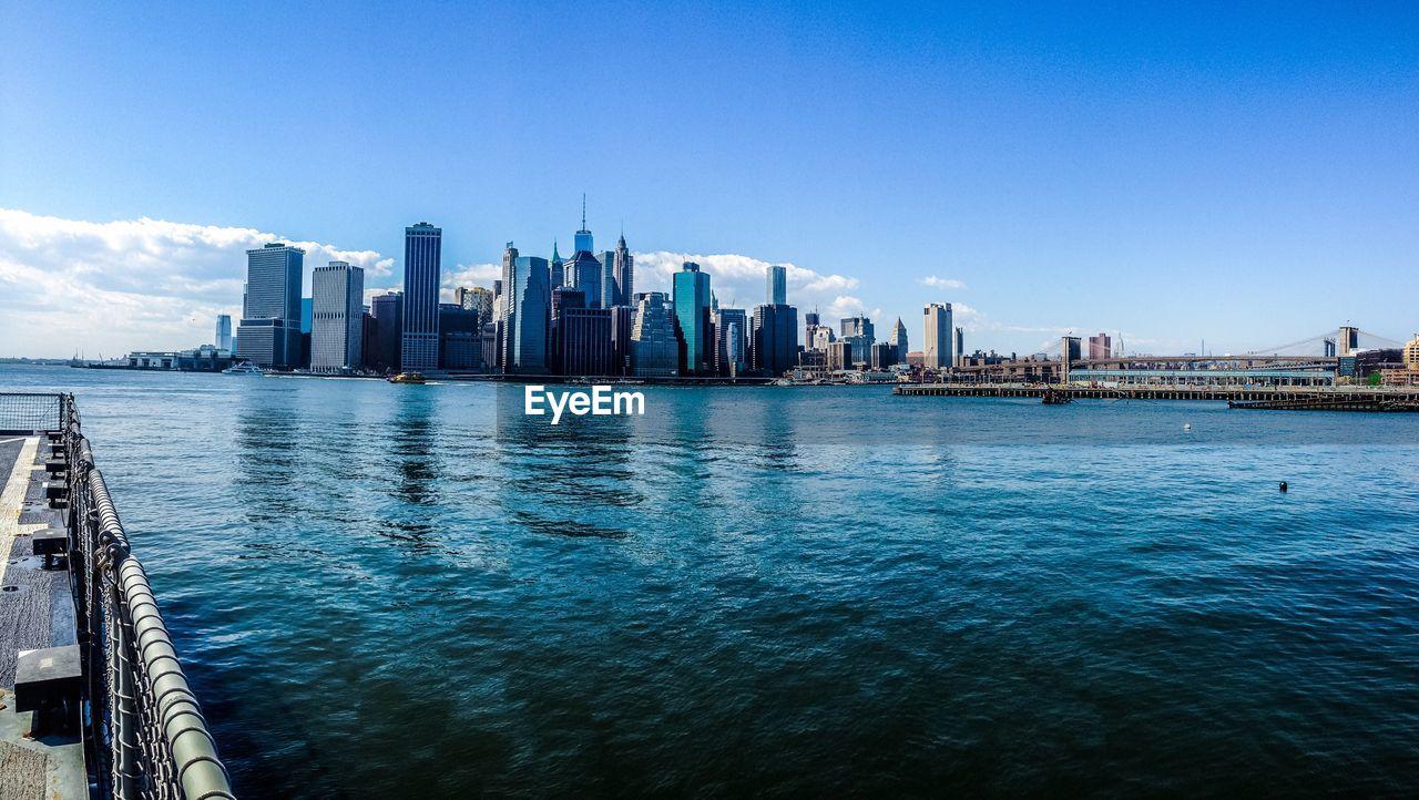 Sea By Modern Buildings Against Blue Sky