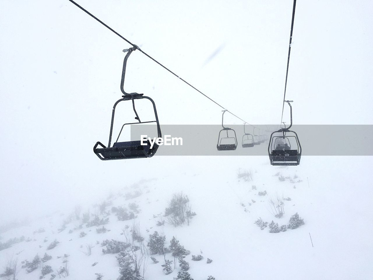cold temperature, snow, winter, ski lift, cable car, overhead cable car, nature, transportation, land, scenics - nature, sky, mode of transportation, day, field, no people, beauty in nature, white color, fog, hanging, outdoors, snowcapped mountain, snowing