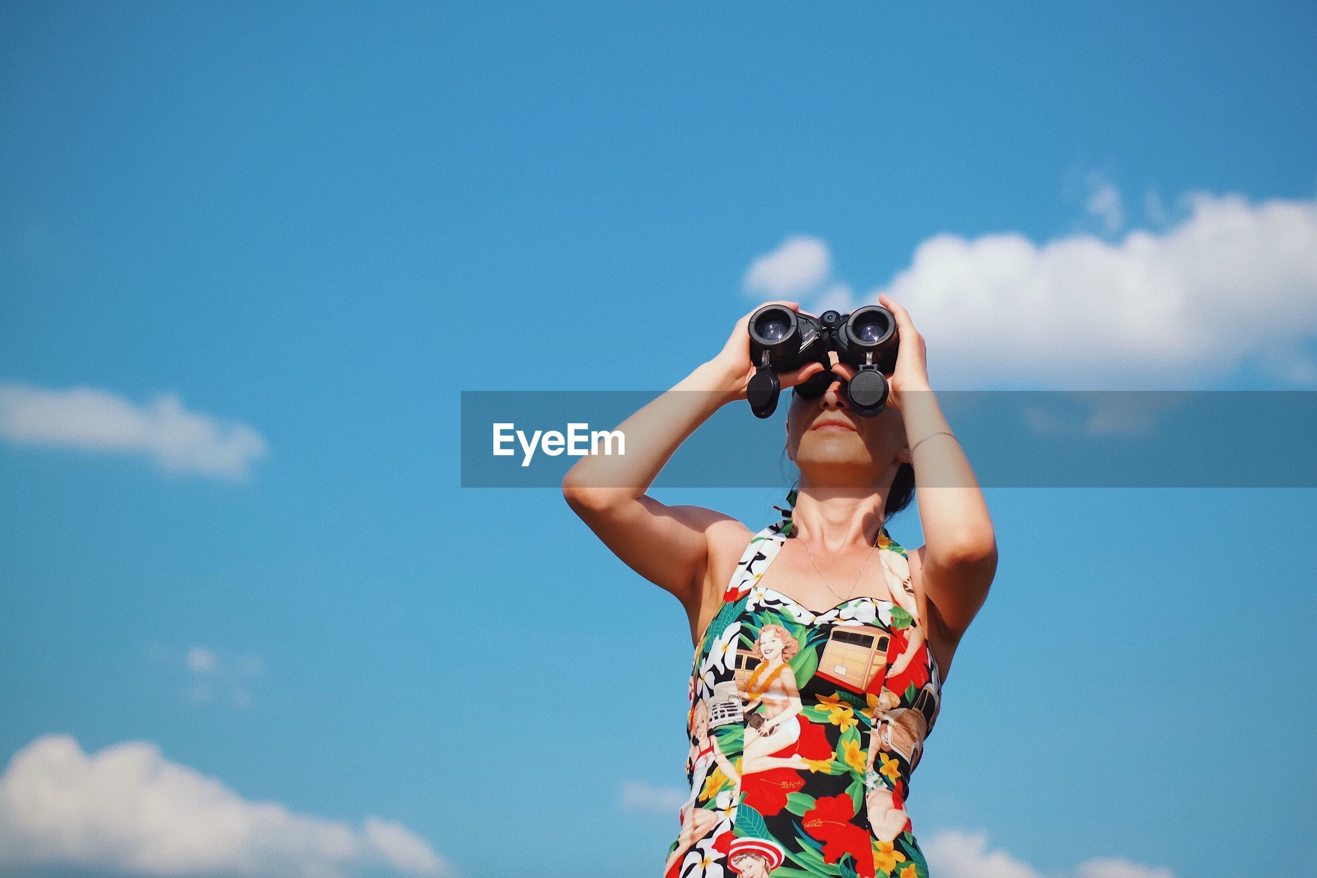 Low angle view of woman looking through binoculars against blue sky
