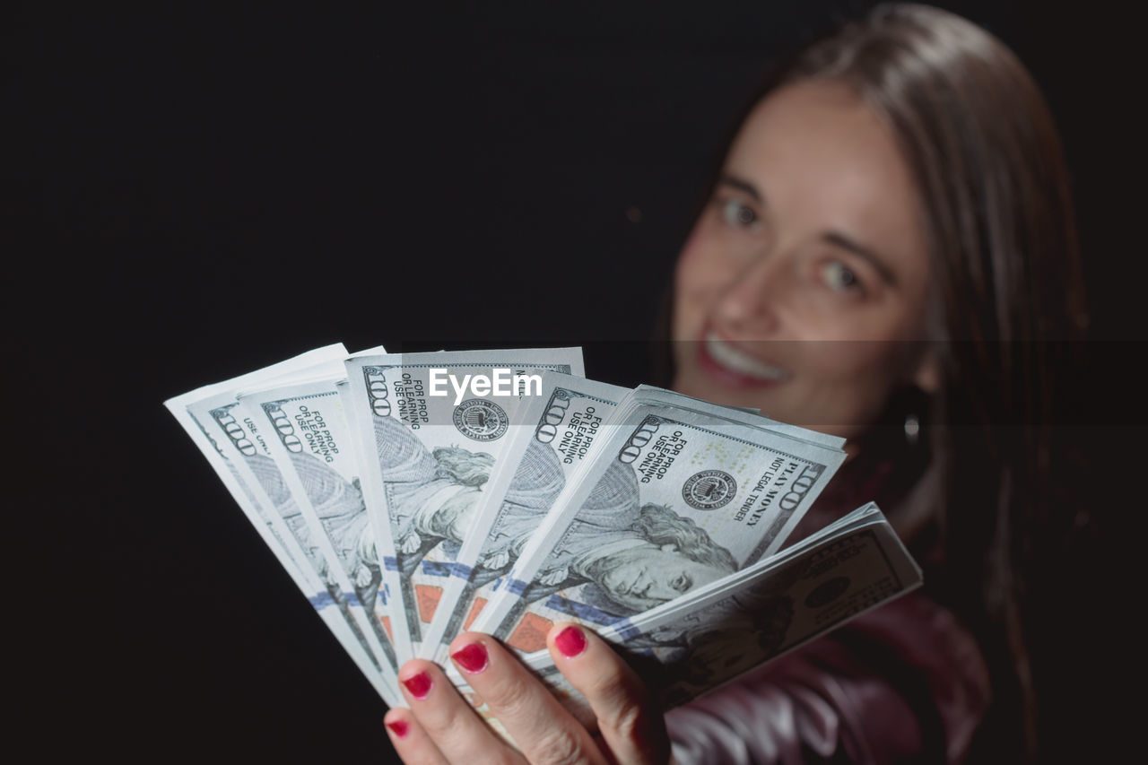 Portrait of smiling woman showing currency while standing against black background