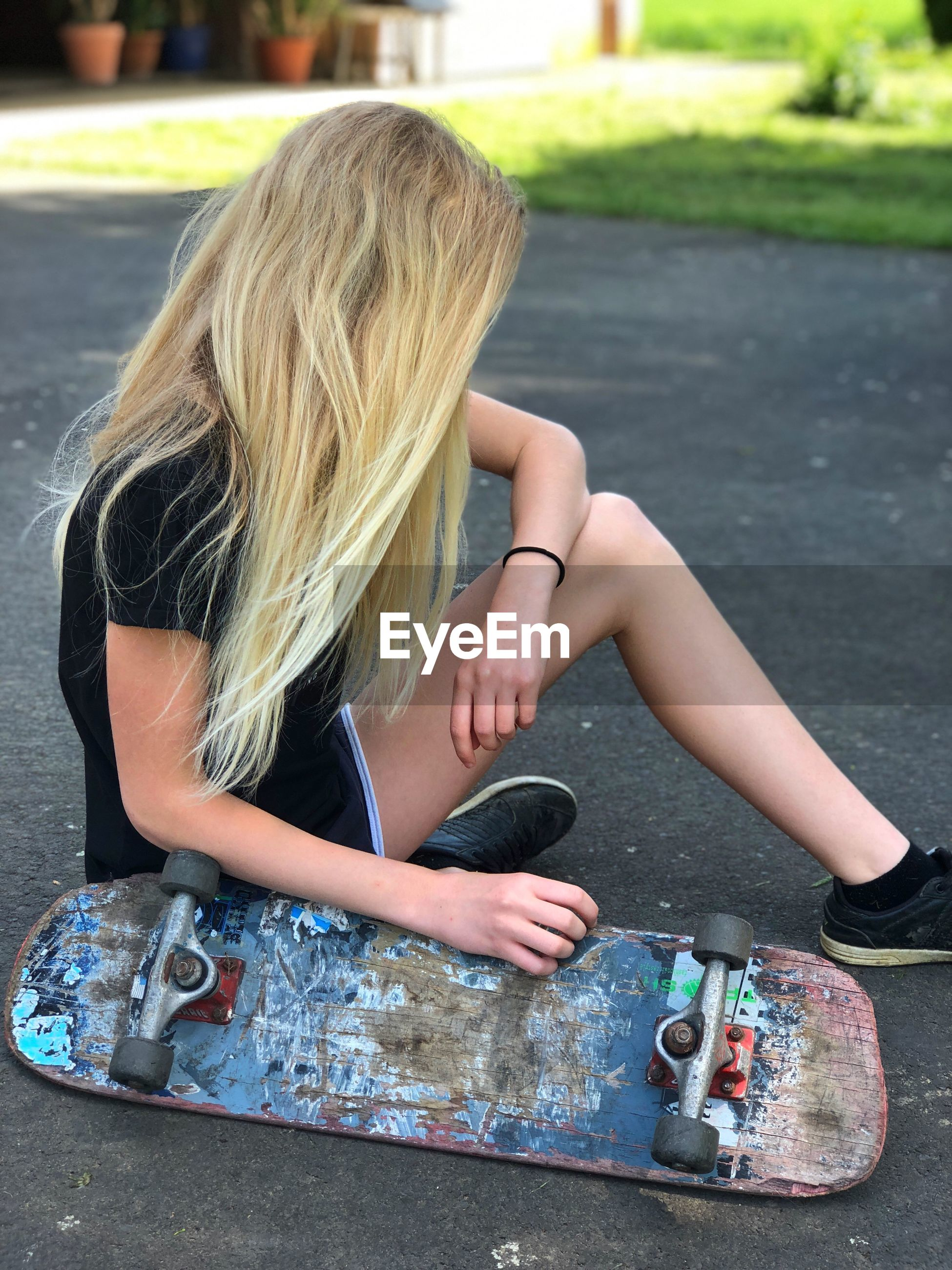 Side view of teenage girl with skateboard sitting on road in city