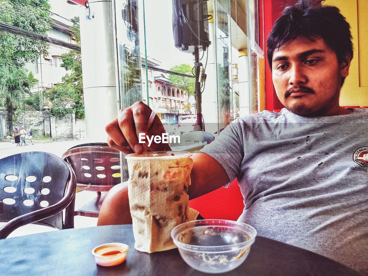 Close-up of man sitting at cafe