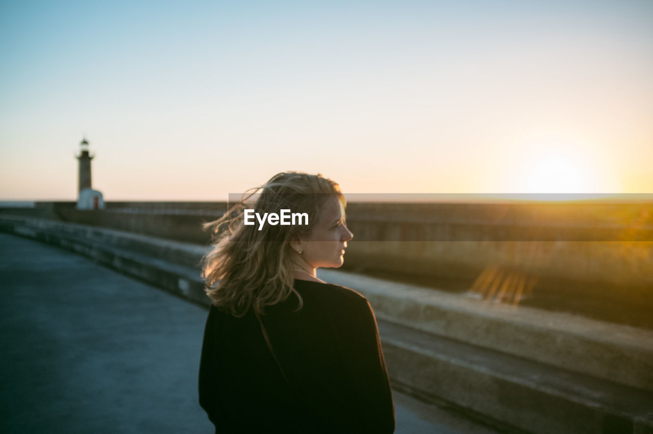 Woman looking away at promenade against clear sky during sunset