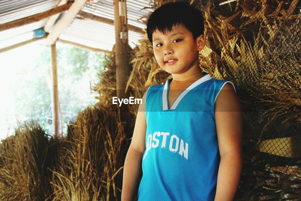 Portrait of boy standing against hay