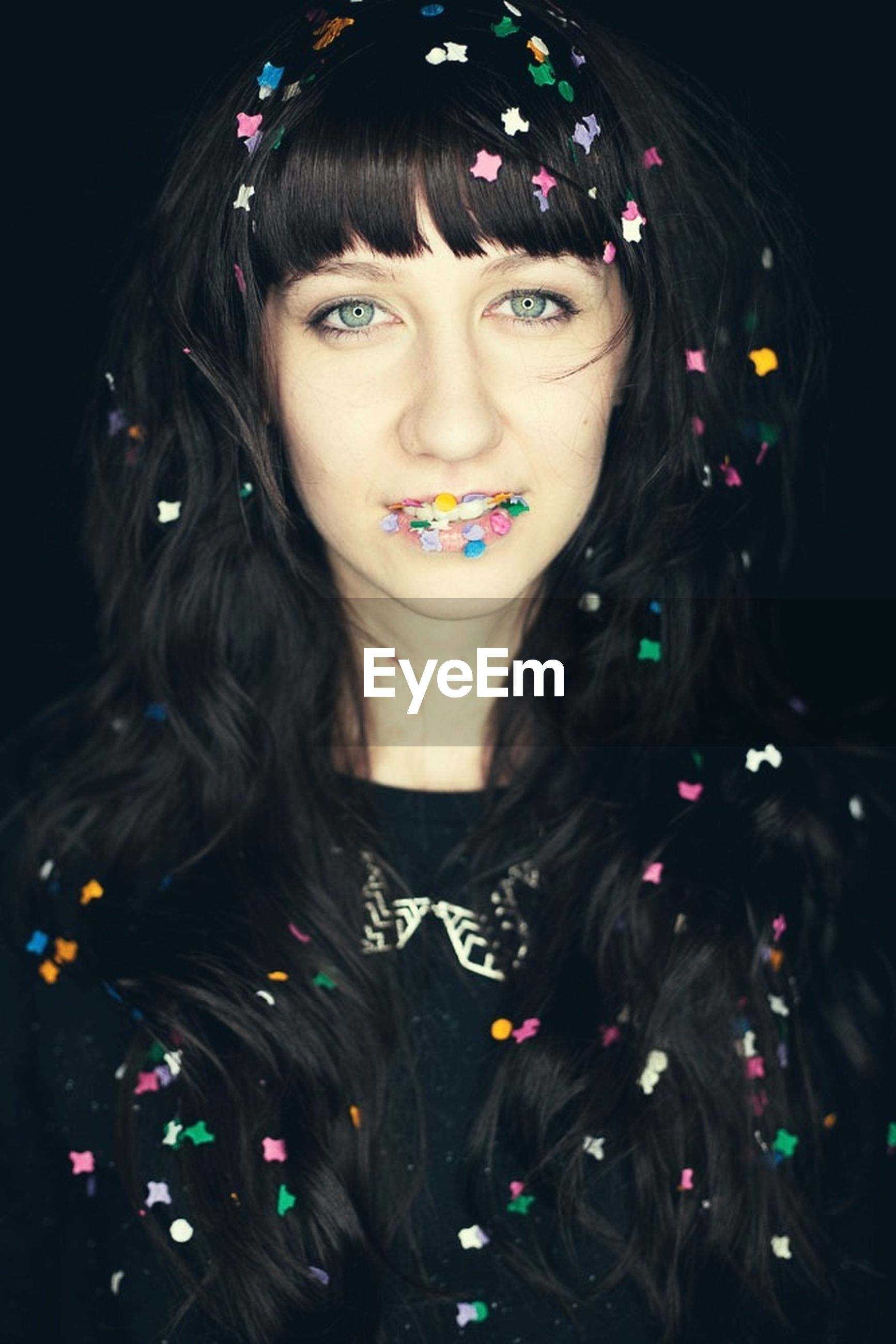 Portrait of a beautiful young woman with confetti over black background