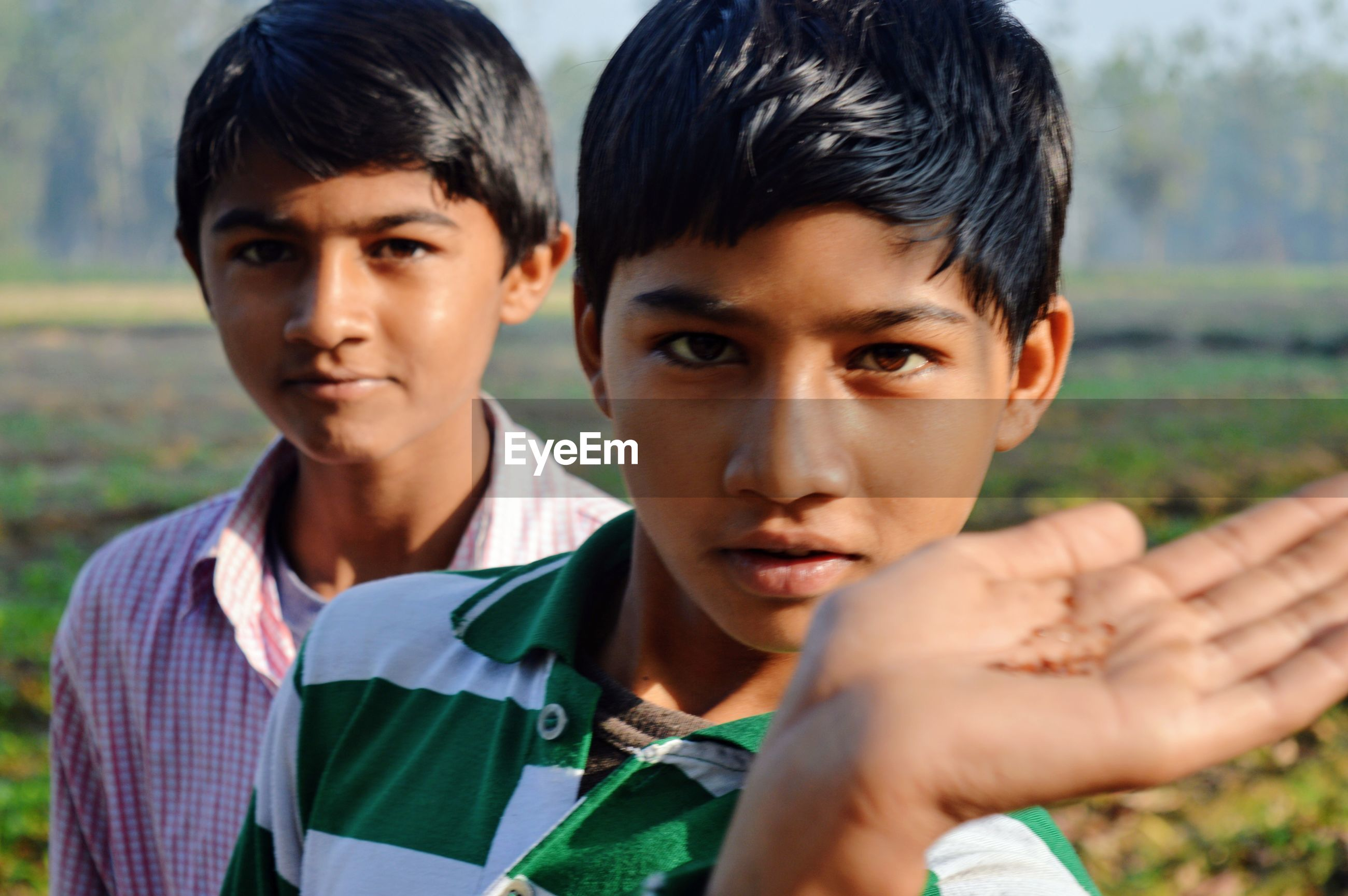 Portrait of boy standing with brother on field