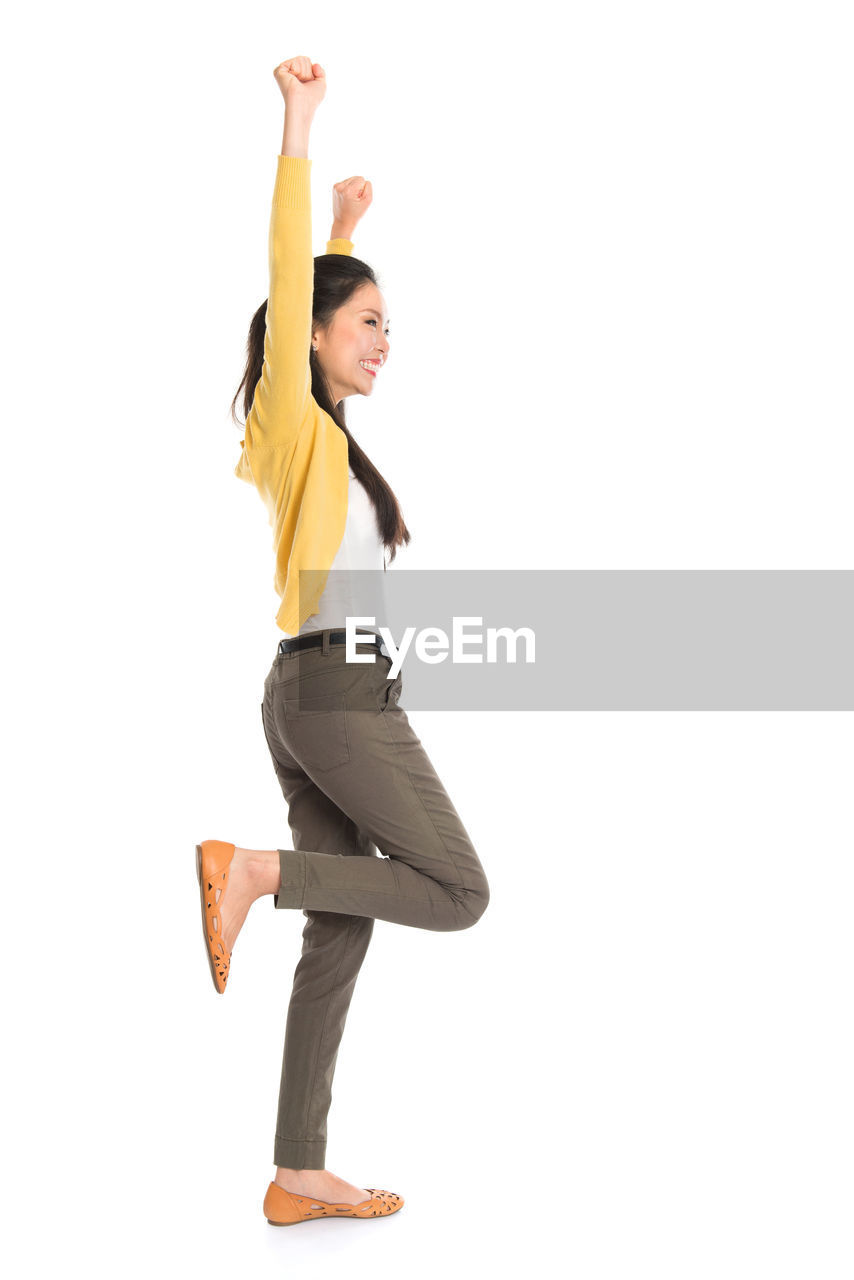full length, studio shot, white background, one person, indoors, human arm, lifestyles, cut out, copy space, arms raised, dancing, happiness, casual clothing, smiling, young adult, side view, limb, young women, skill, leg, excitement