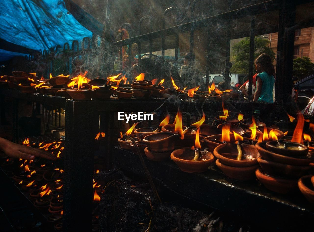 Lit candles in temple against railing