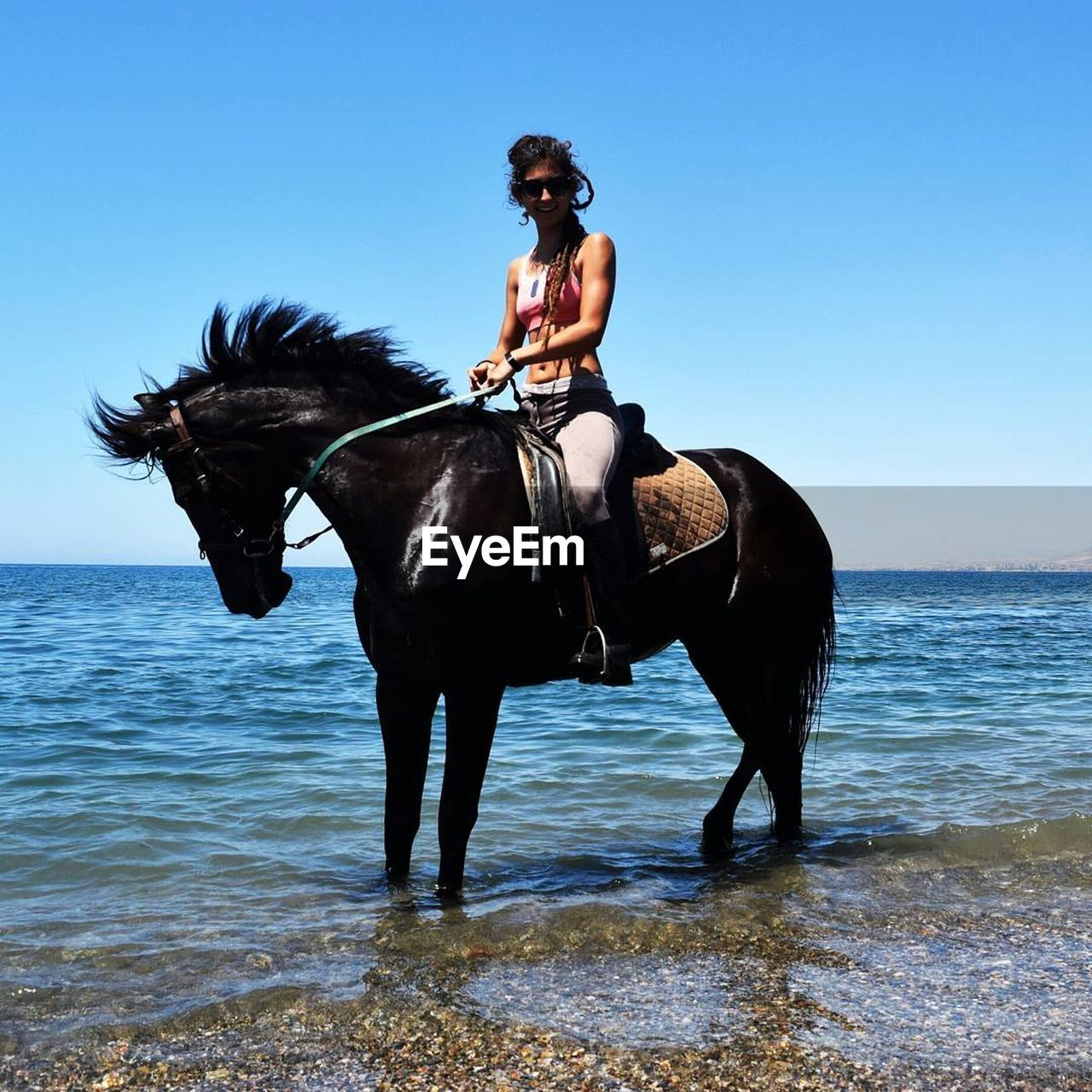 Woman riding horse in sea