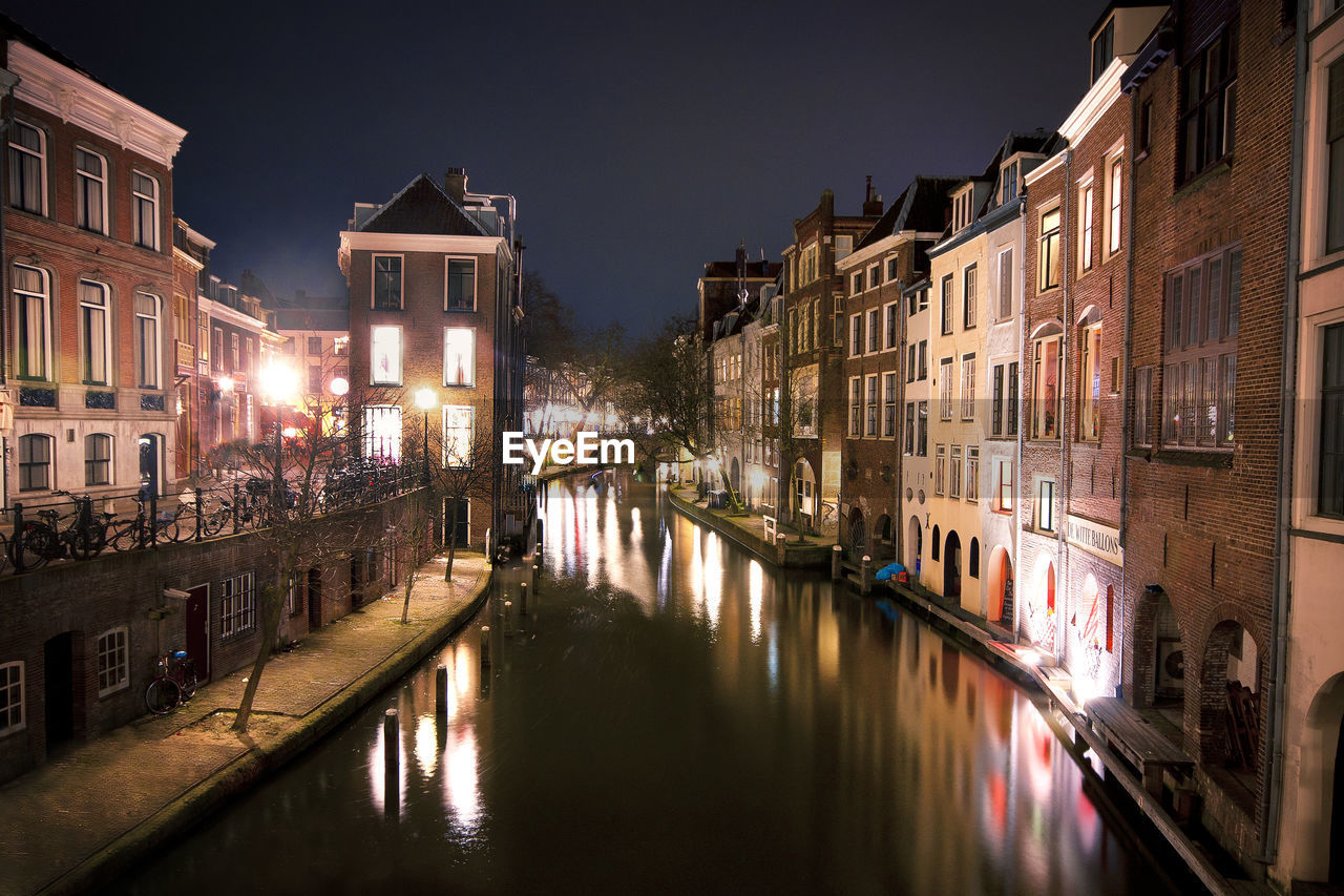 architecture, building exterior, water, built structure, illuminated, canal, night, city, building, reflection, waterfront, nature, residential district, nautical vessel, sky, transportation, street, mode of transportation, no people