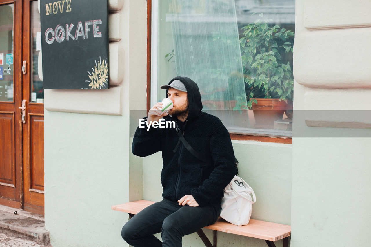 Man drinking coffee in cup while sitting on bench