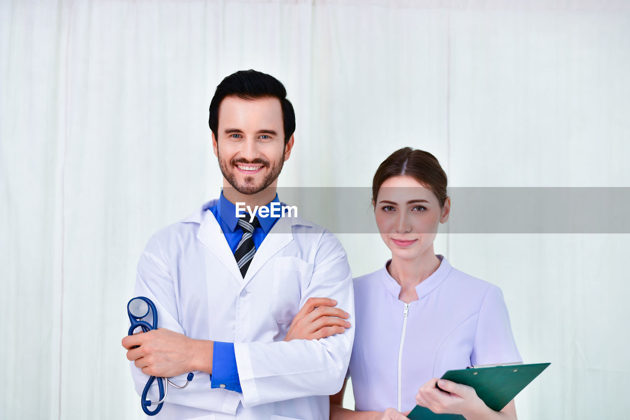 smiling, portrait, young adult, front view, young men, looking at camera, adult, indoors, clothing, occupation, holding, two people, waist up, standing, lab coat, women, healthcare and medicine, doctor, men, coworker, responsibility