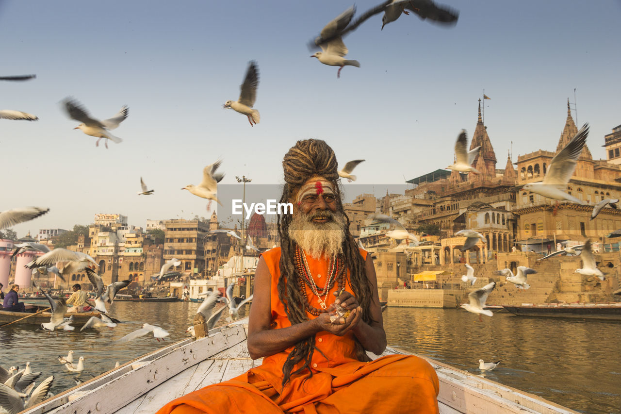 Birds Flying Over Sadhu On Boat In Sea Against Sky