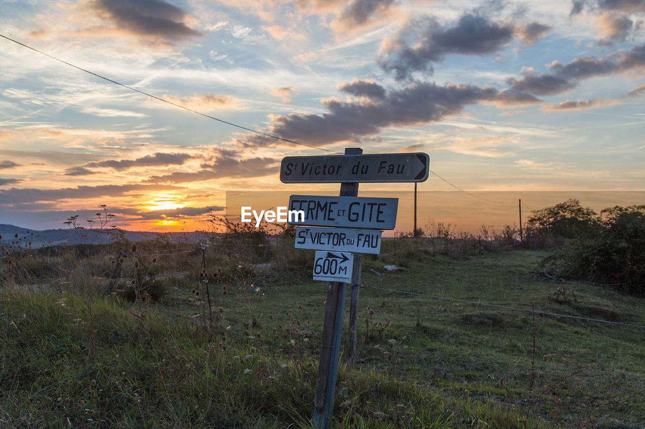 communication, western script, text, guidance, sky, field, nature, no people, cloud - sky, road sign, sunset, landscape, grass, outdoors, beauty in nature, scenics, day