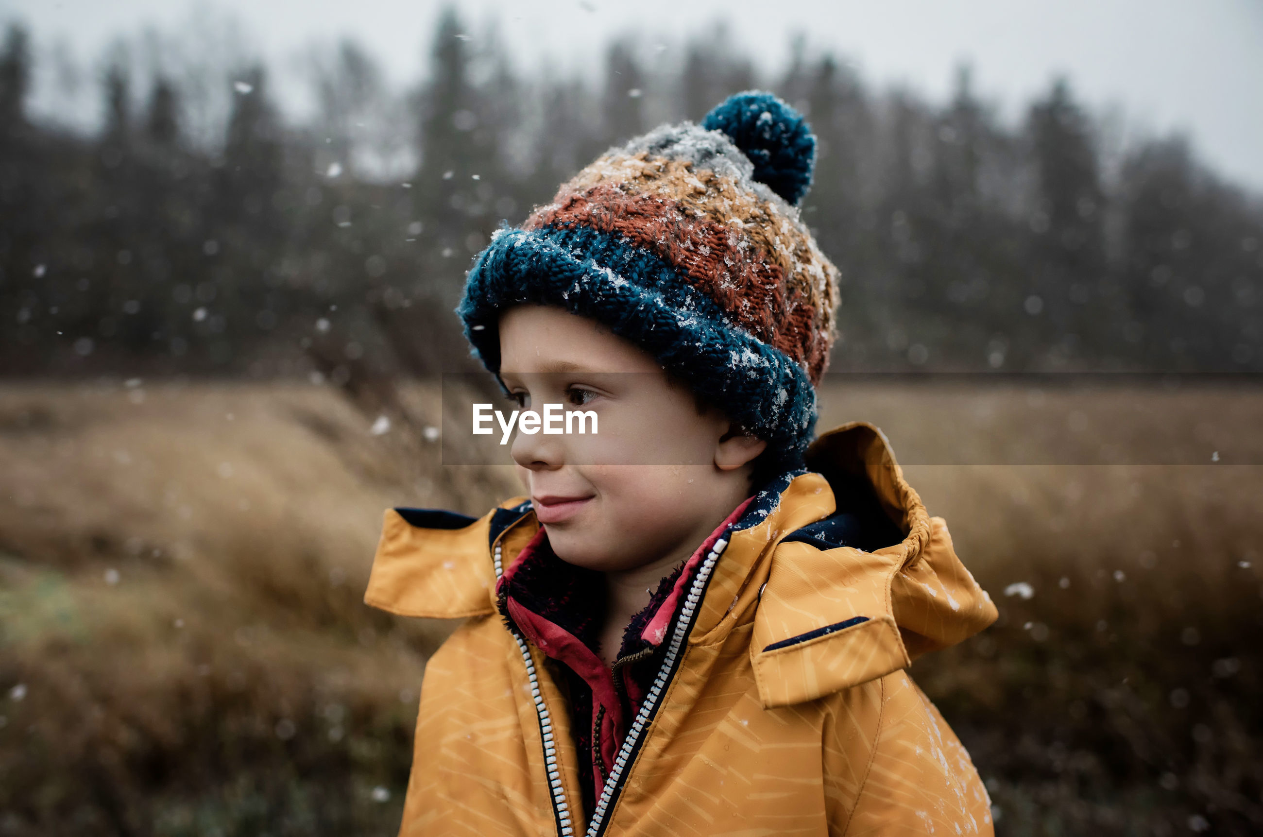 PORTRAIT OF BOY LOOKING AT SNOW