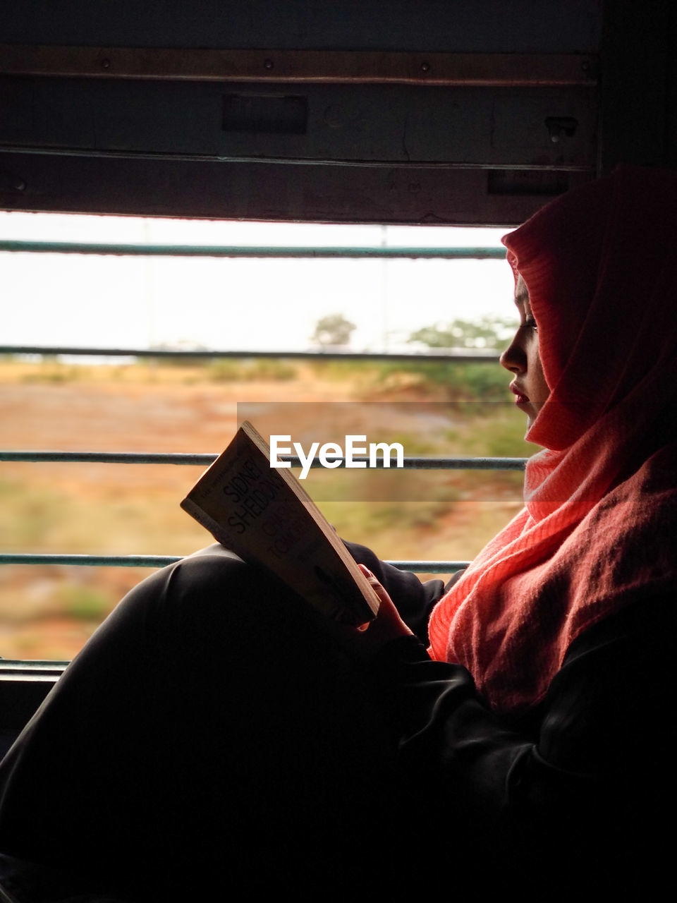 Side View Of Woman Reading Book While Sitting In Train