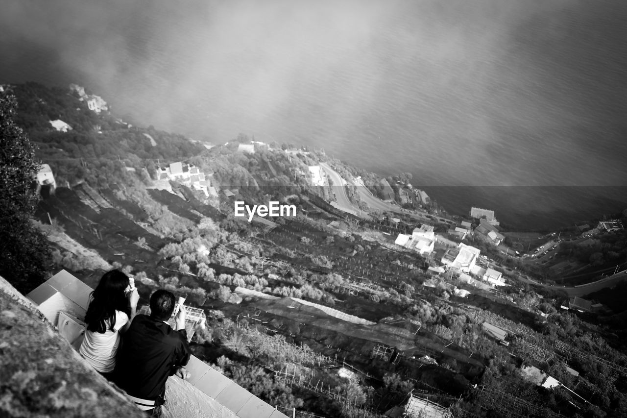 High angle view of couple looking at sea by mountain while standing in balcony