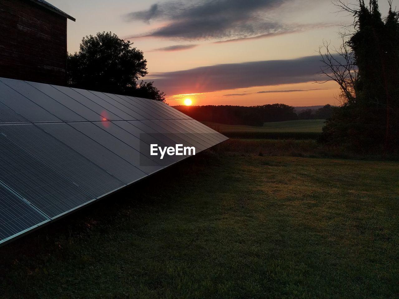 sunset, sun, solar energy, solar panel, sky, nature, cloud - sky, tree, grass, outdoors, no people, alternative energy, beauty in nature, scenics, solar equipment, day