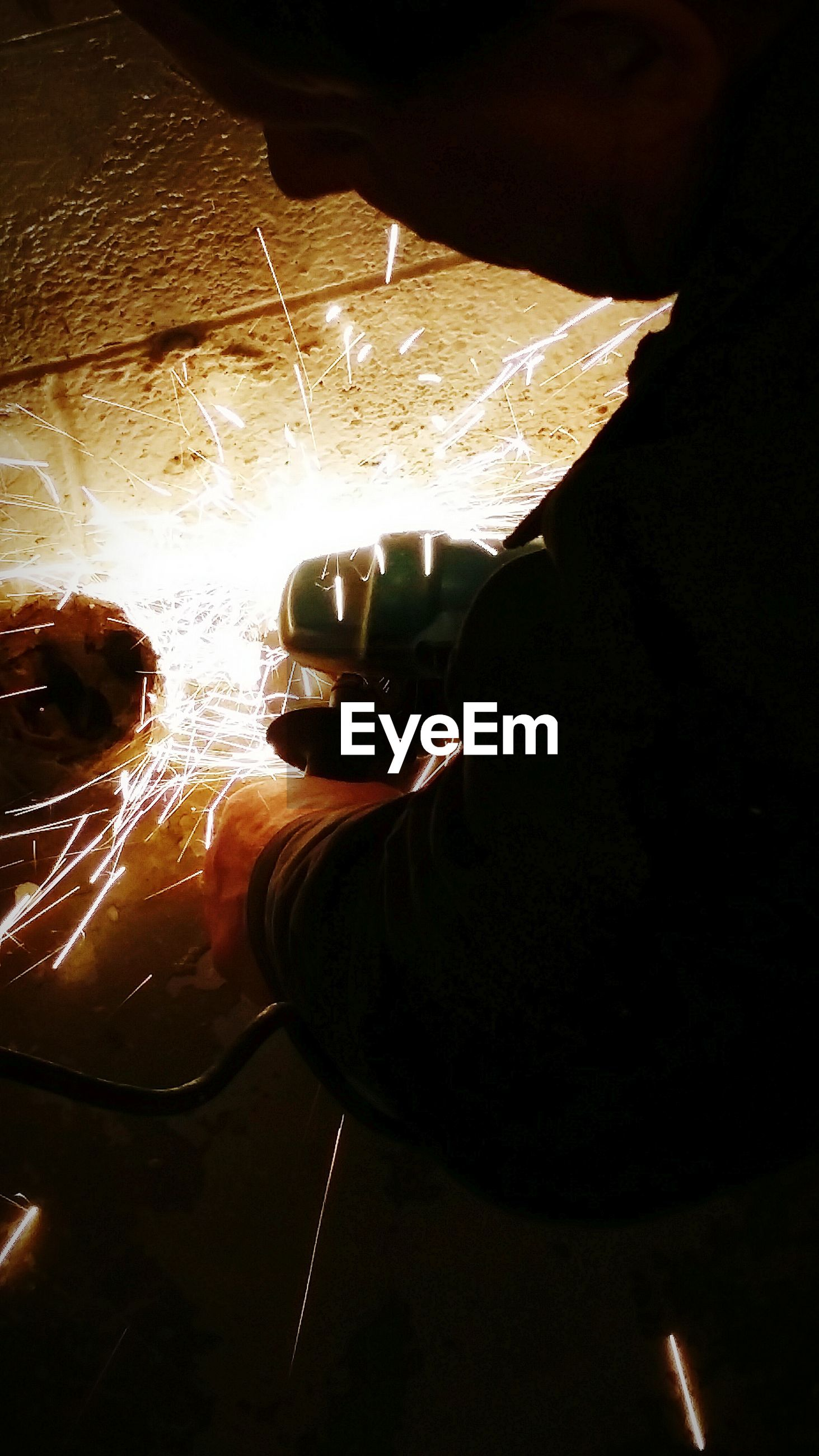 Close-up of man cutting iron with grinder