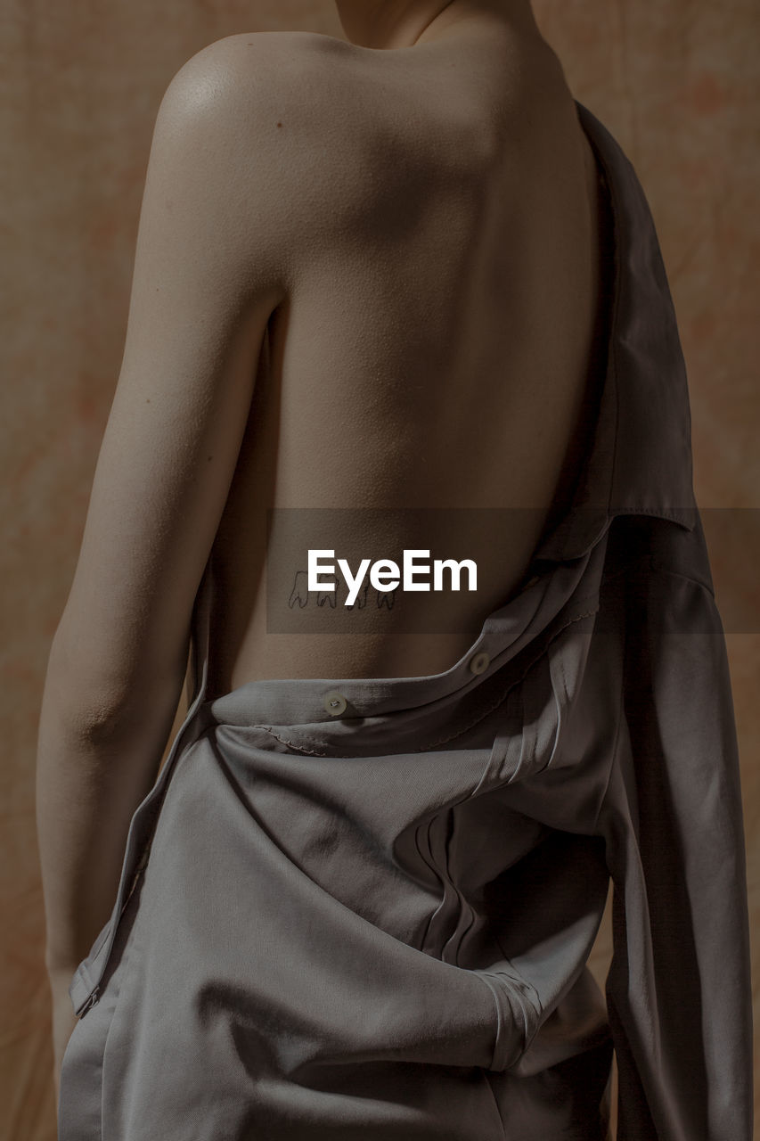 one person, midsection, indoors, clothing, adult, human body part, real people, women, front view, shirtless, body part, text, lifestyles, standing, focus on foreground, obscured face