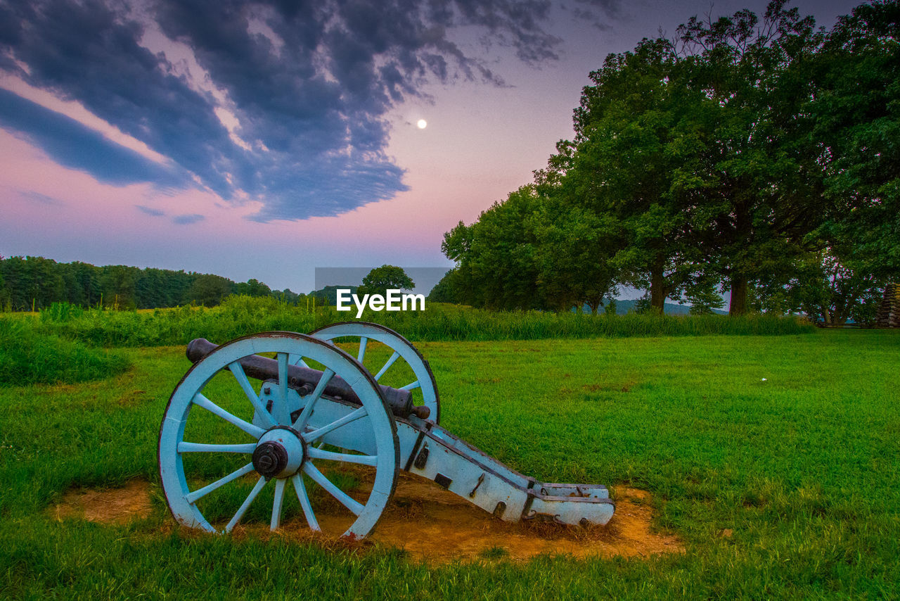 field, grass, weapon, tree, wheel, nature, cannon, canon, no people, cloud - sky, history, tranquility, beauty in nature, green color, scenics, sky, landscape, growth, tranquil scene, wagon wheel, war, outdoors, day, military