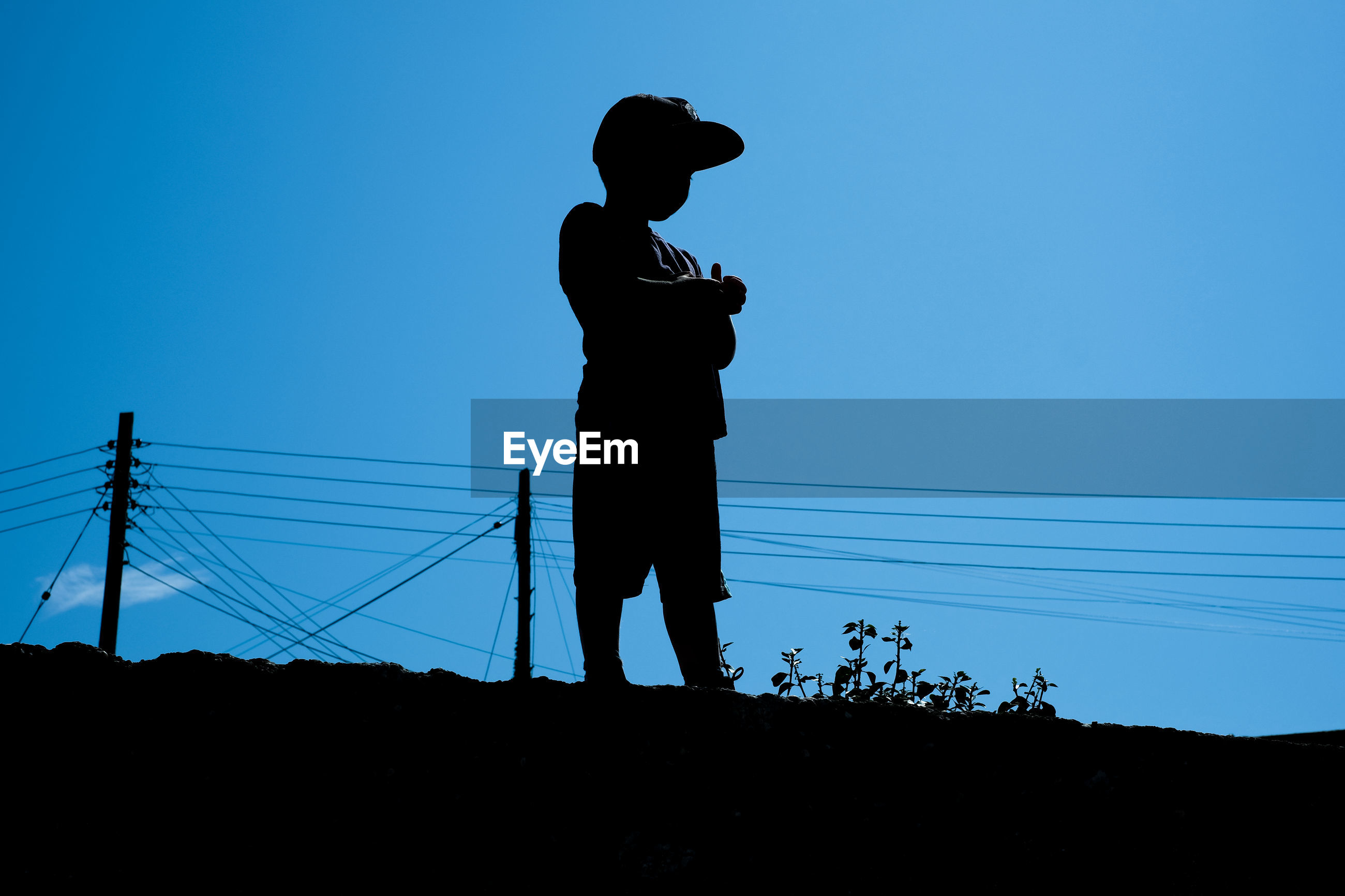Low angle view of silhouette boy standing against clear blue sky