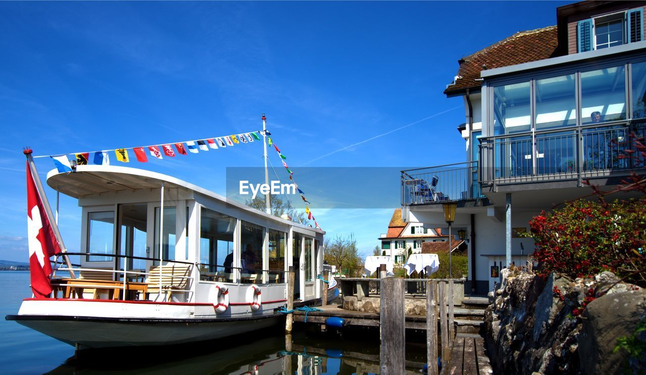 Boat Moored In River By Hotel Against Blue Sky
