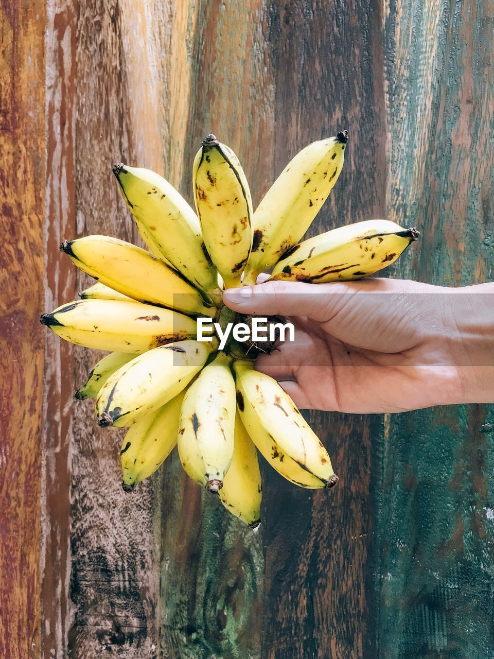 yellow, hand, banana, human hand, food, freshness, healthy eating, one person, fruit, human body part, food and drink, wellbeing, wood - material, real people, holding, unrecognizable person, tropical fruit, bunch, finger, ripe