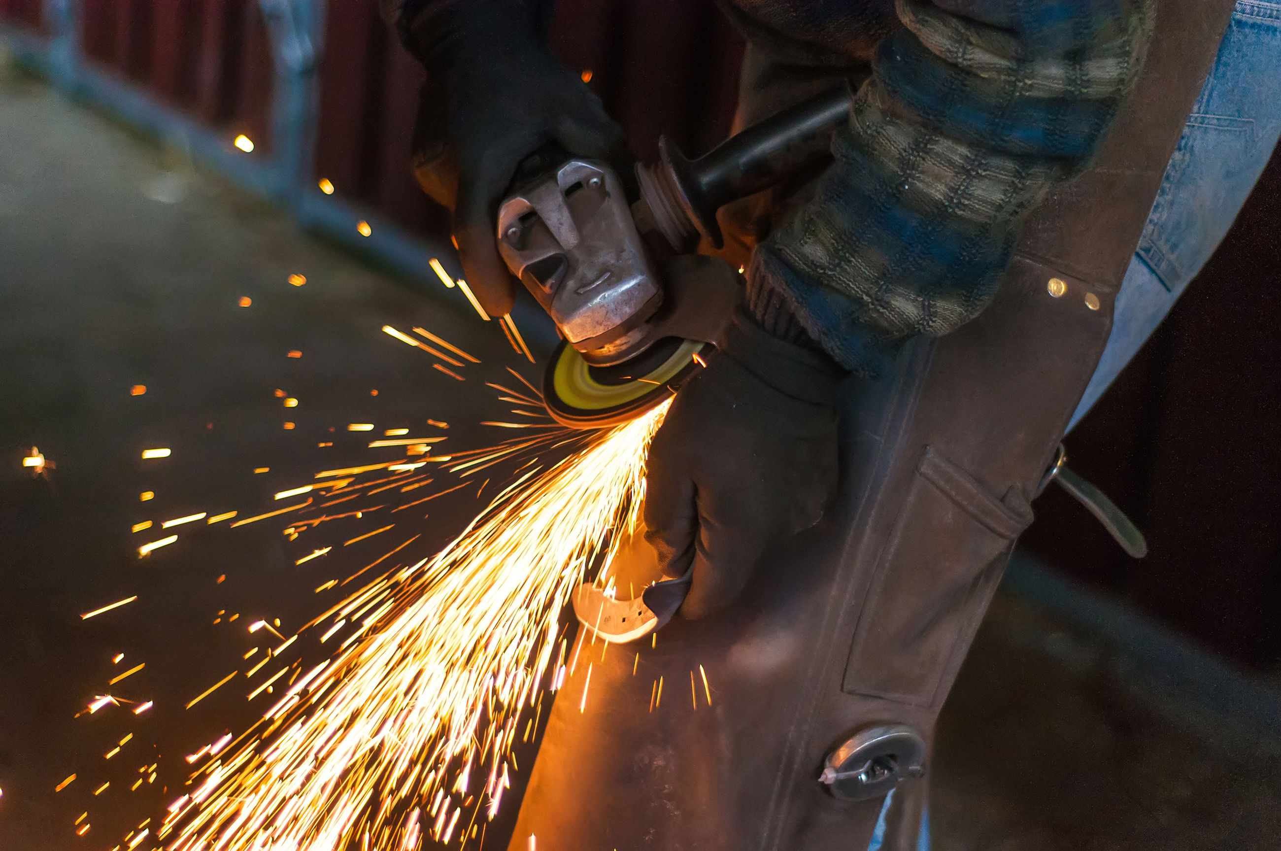 Midsection of worker grinding metal in industry
