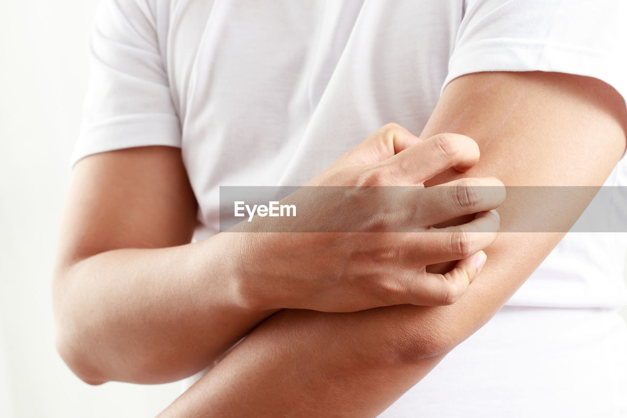 MIDSECTION OF WOMAN SITTING ON WHITE BACKGROUND