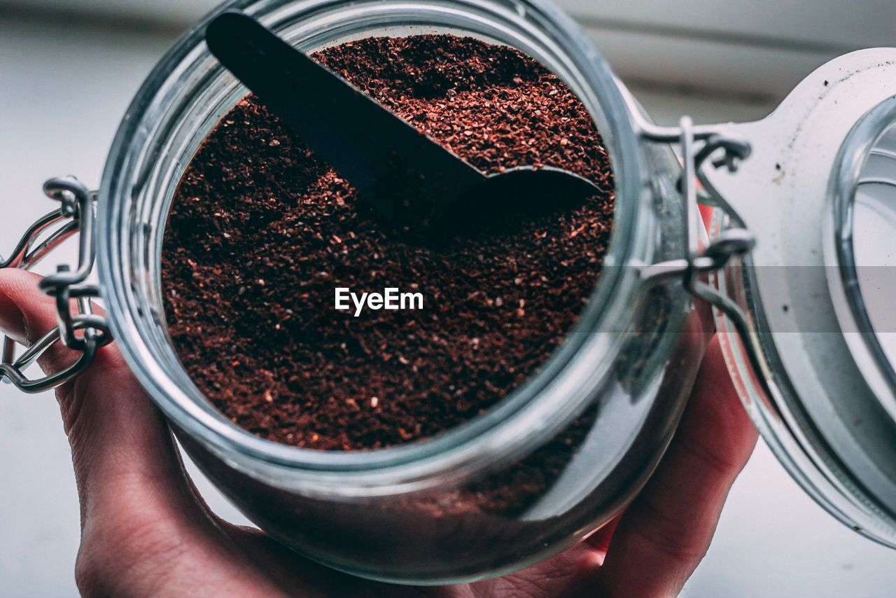 human hand, hand, holding, one person, human body part, real people, close-up, indoors, food and drink, food, high angle view, unrecognizable person, preparation, personal perspective, ground coffee, container, freshness, lifestyles, human finger, finger, caffeine