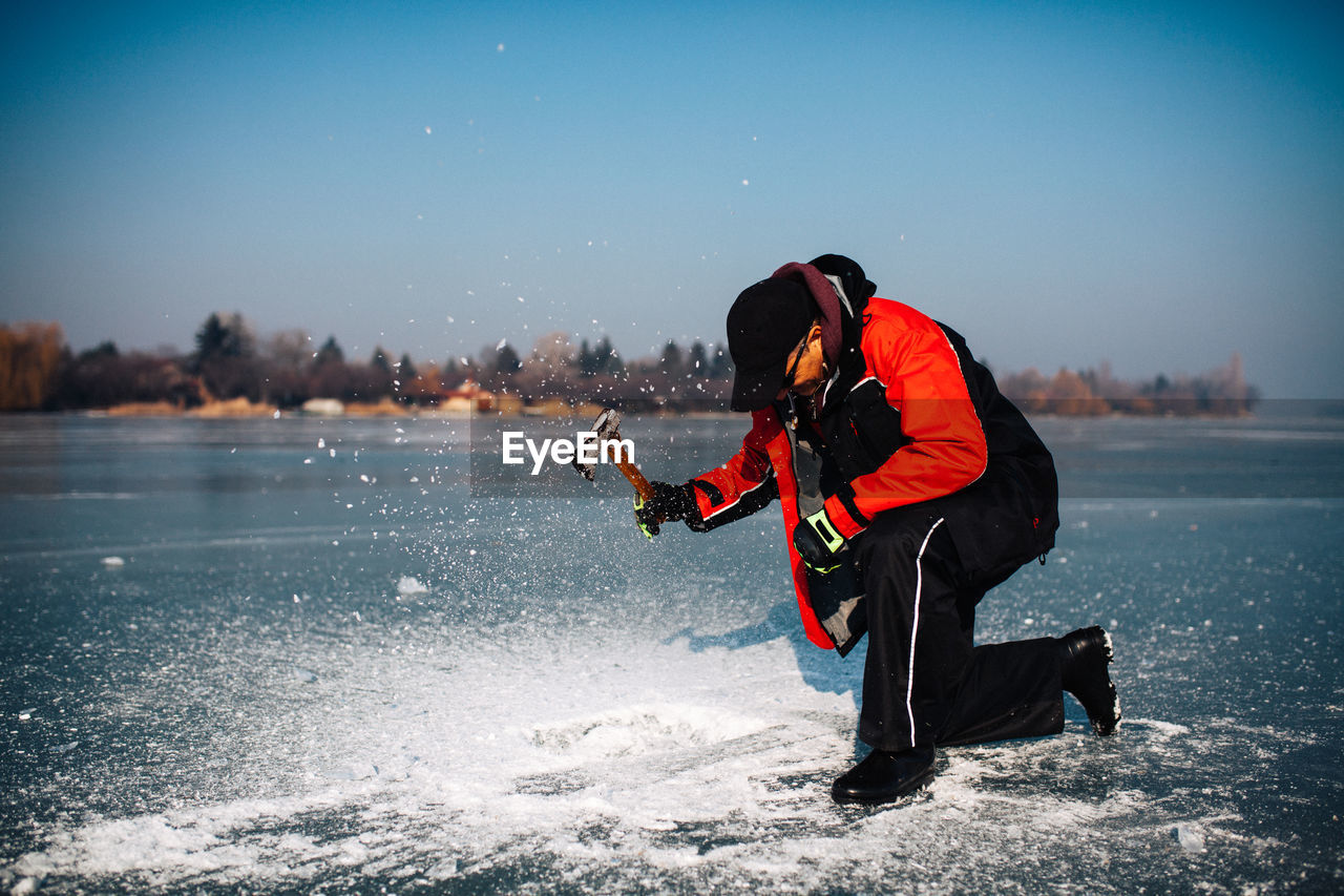 Man with axe on lake