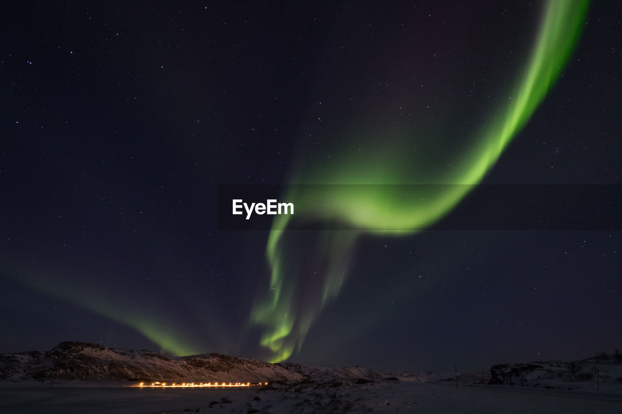 Aurora borealis over landscape against star field at night during winter