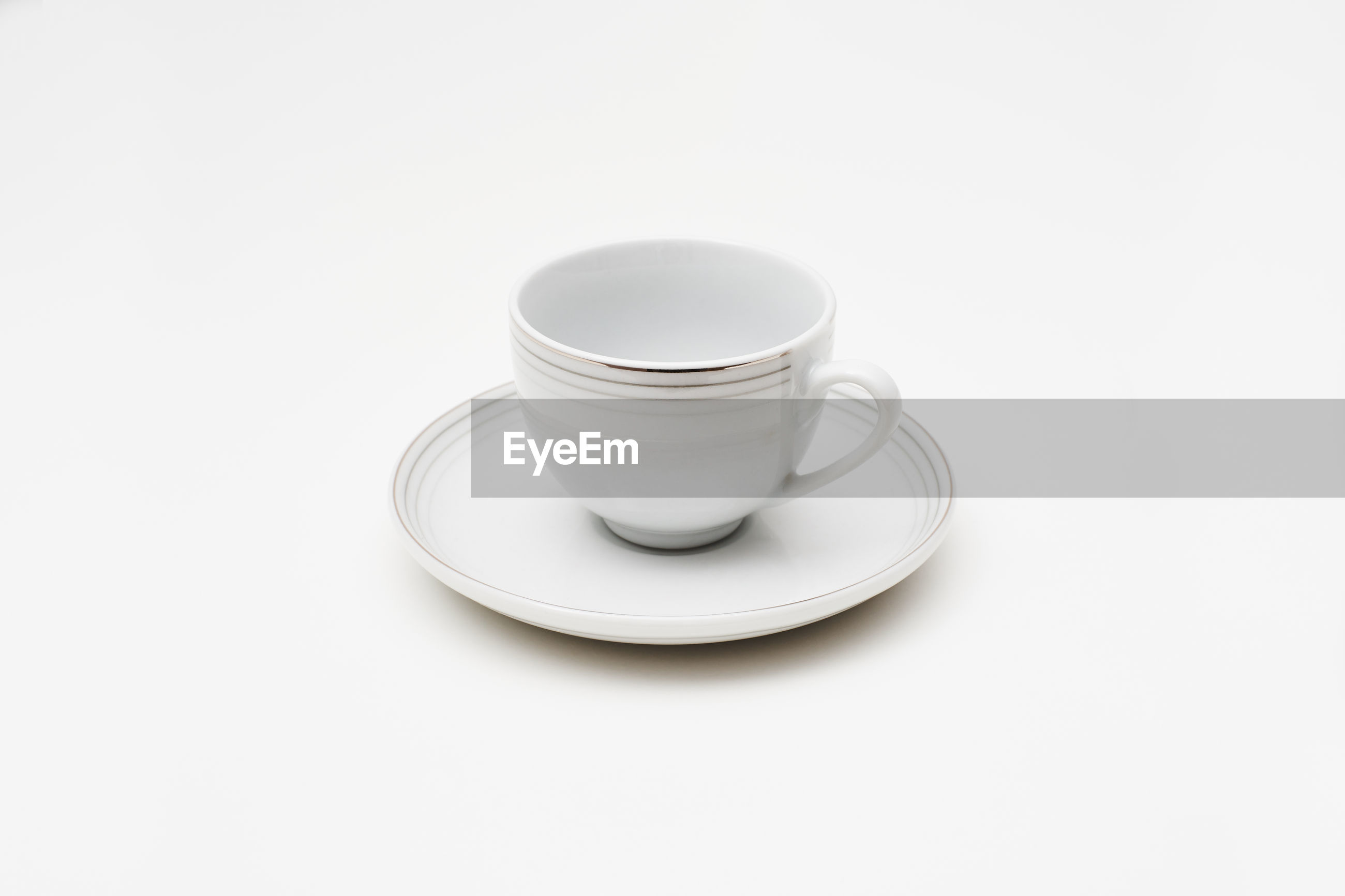 A white cup of coffee with dish or plate isolated on uniform background