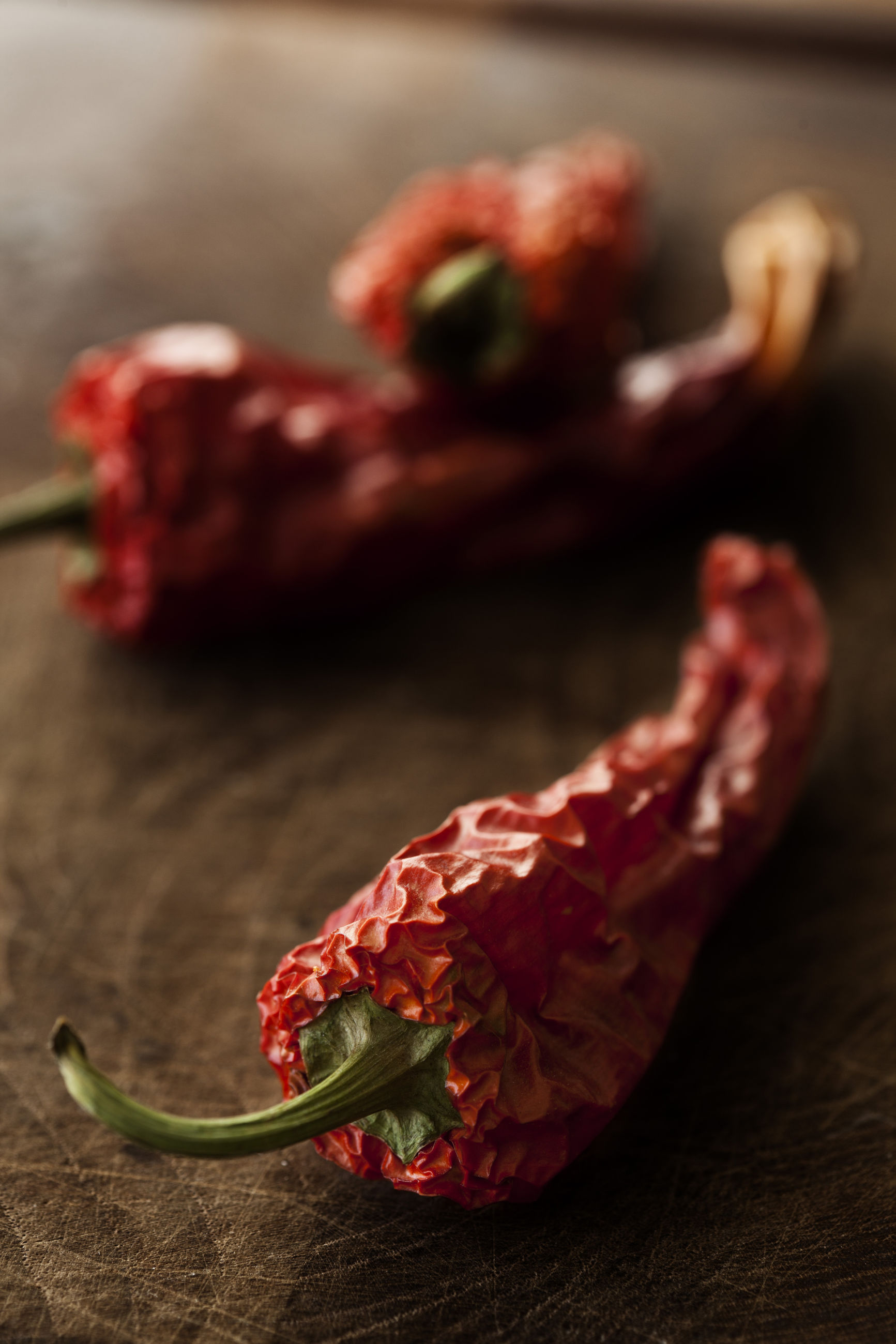CLOSE-UP OF RED CHILI PEPPERS IN CONTAINER ON TABLE
