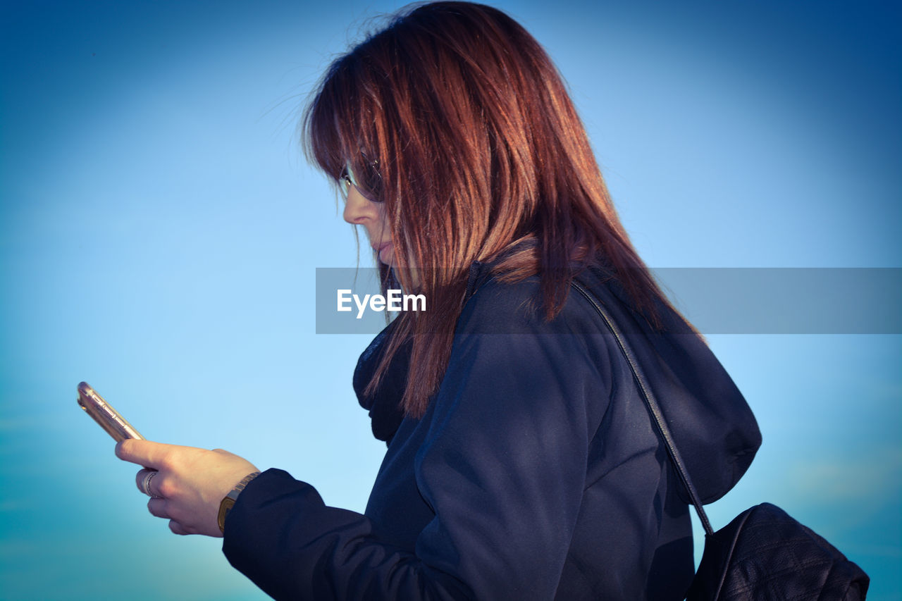 Side view of woman using phone against sky