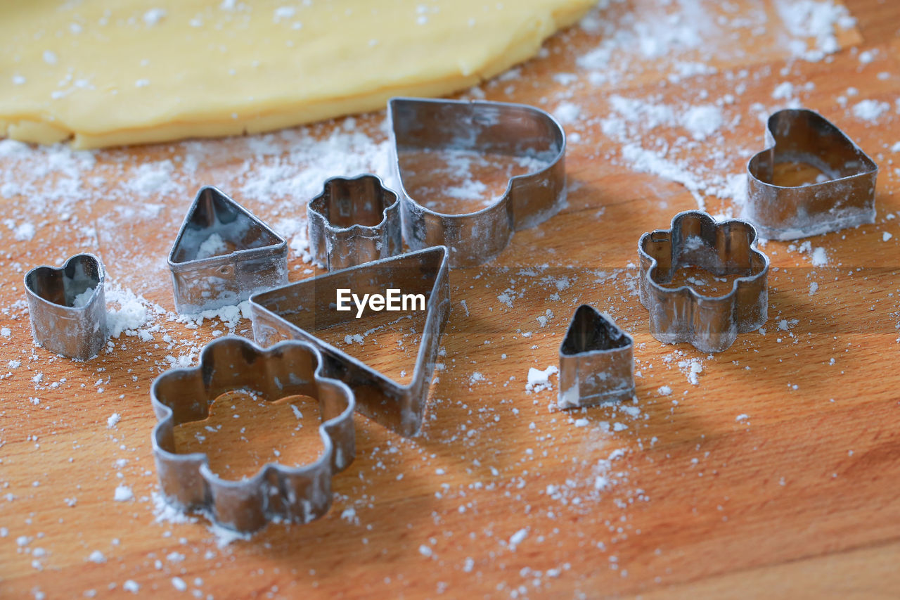 High angle view of pastry cutter and flour on table