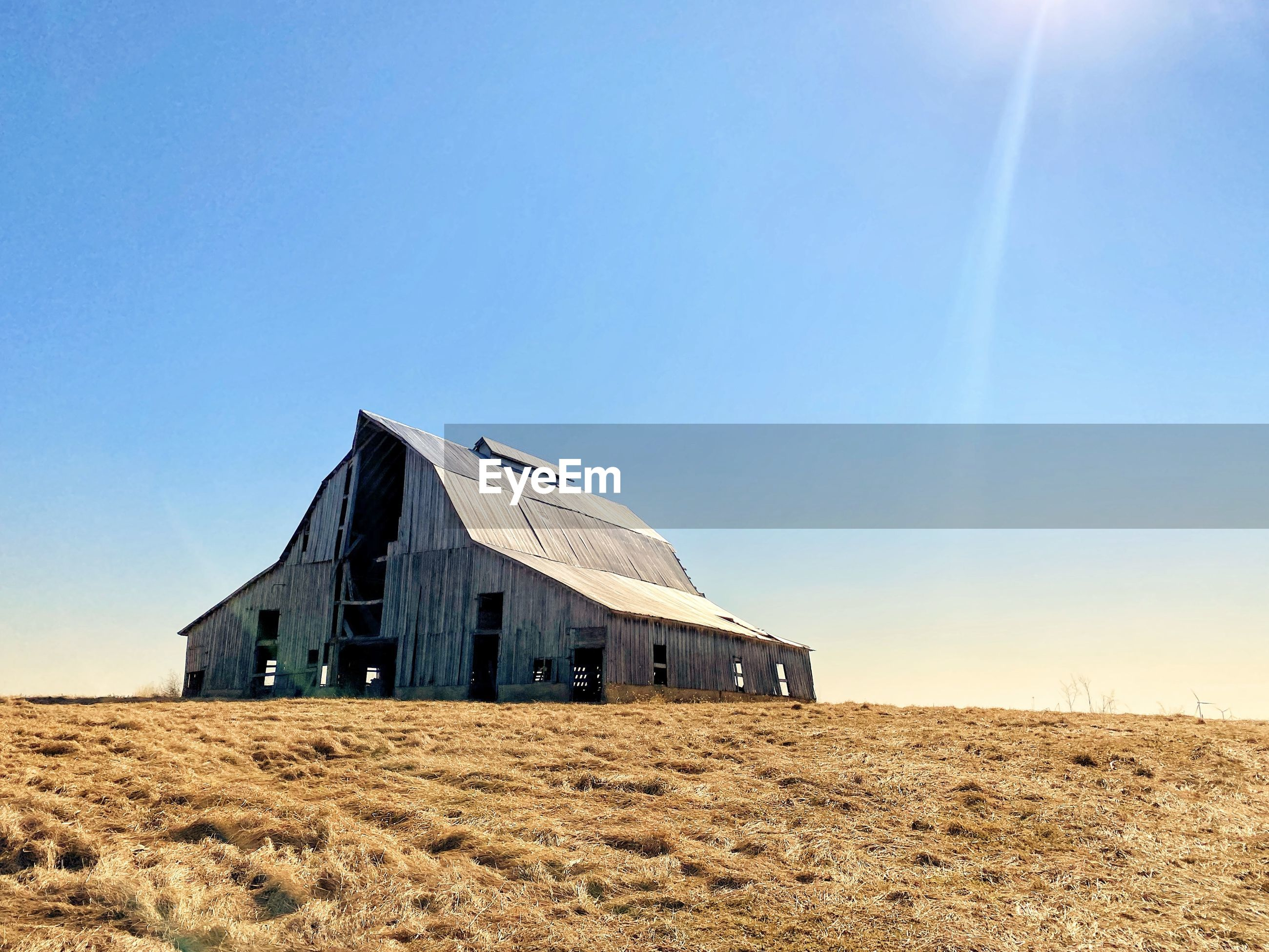 Abandoned building on field against clear blue sky