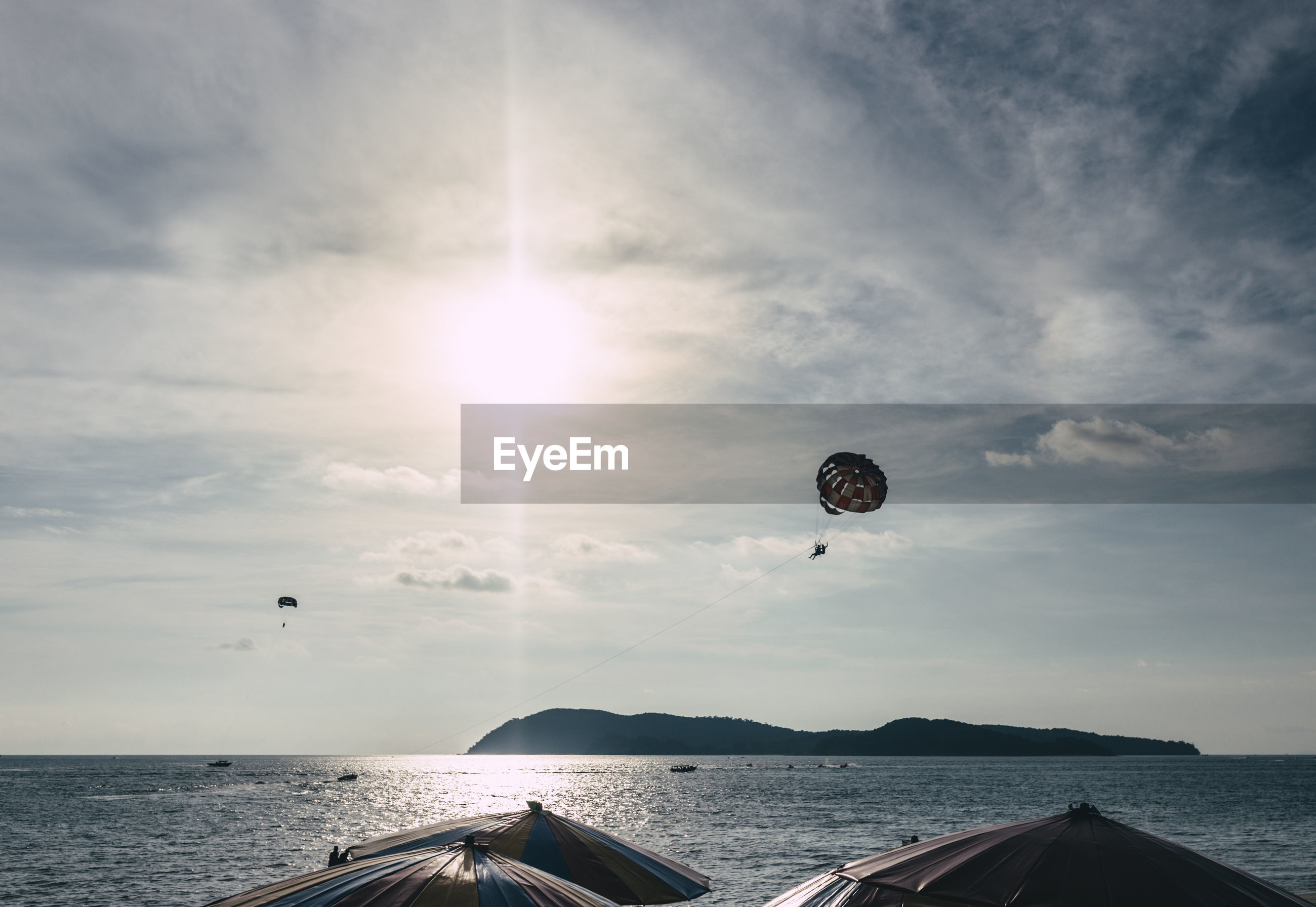 People paragliding over sea against cloudy sky in sunny day