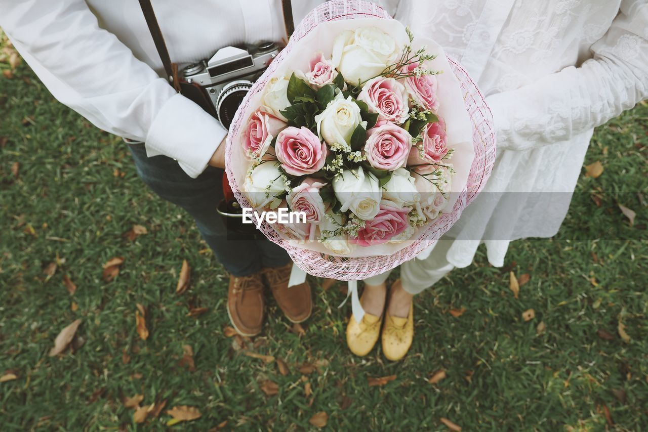 Low Section Of Bride And Groom Holding Bouquet While Standing On Grassy Field