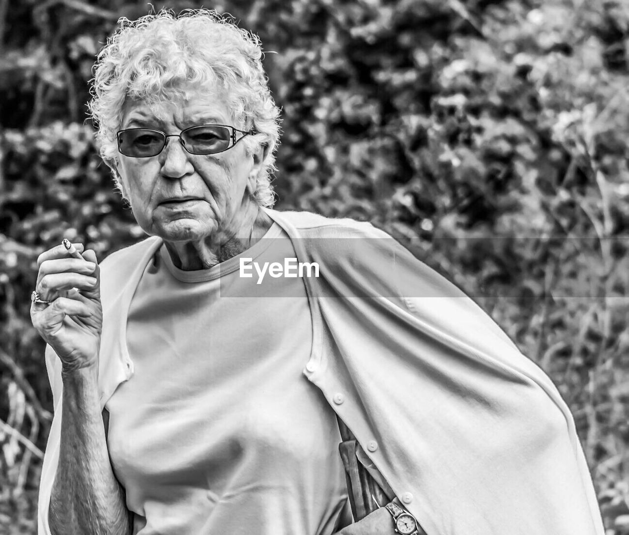 Portrait of senior woman smoking while standing against plant