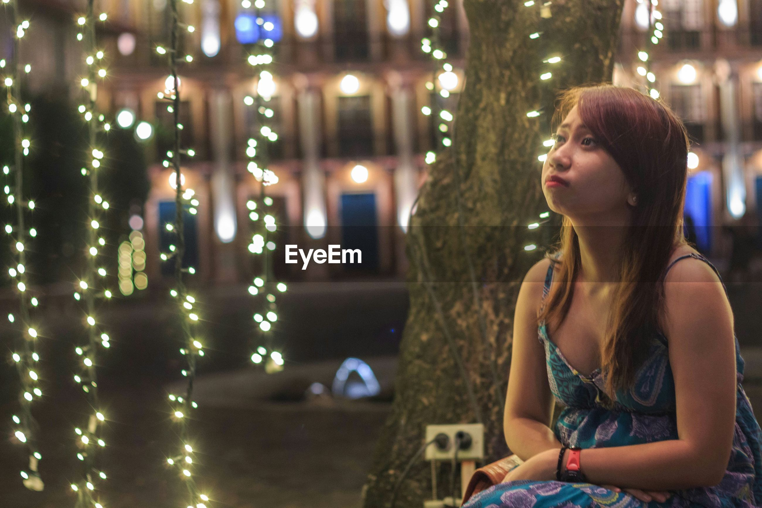 Young woman looking away by illuminated lighting equipment on tree at night